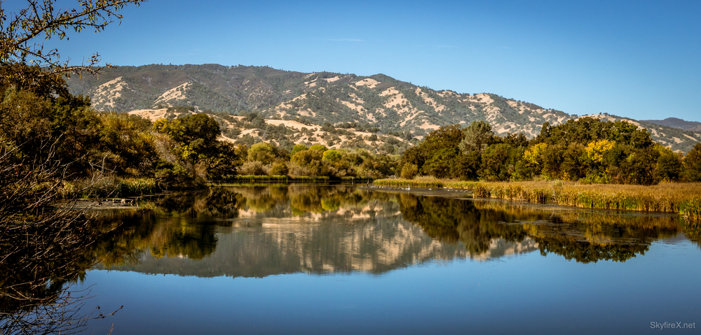 The hills of Napa Valley reflecting in the surface of the lake.