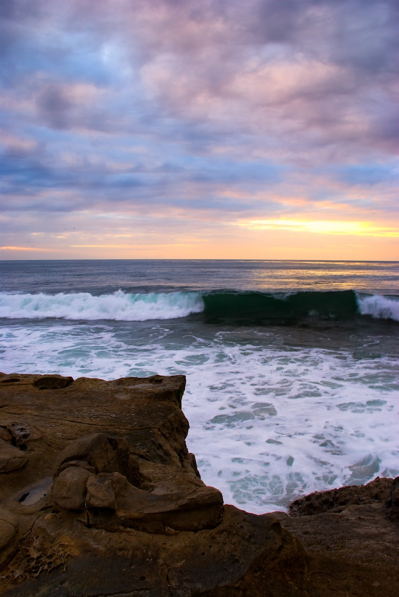 A wave comes to shore during a stunning sunset in La Jolla, CA