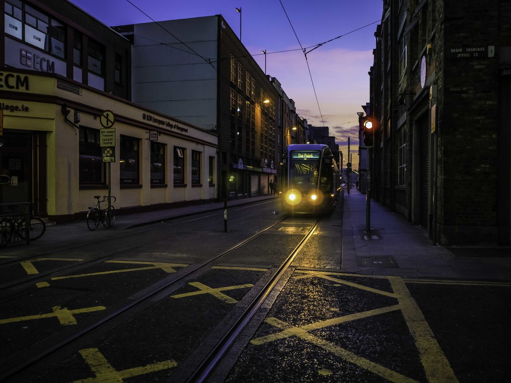 a tram coming down the street with sunset behind it