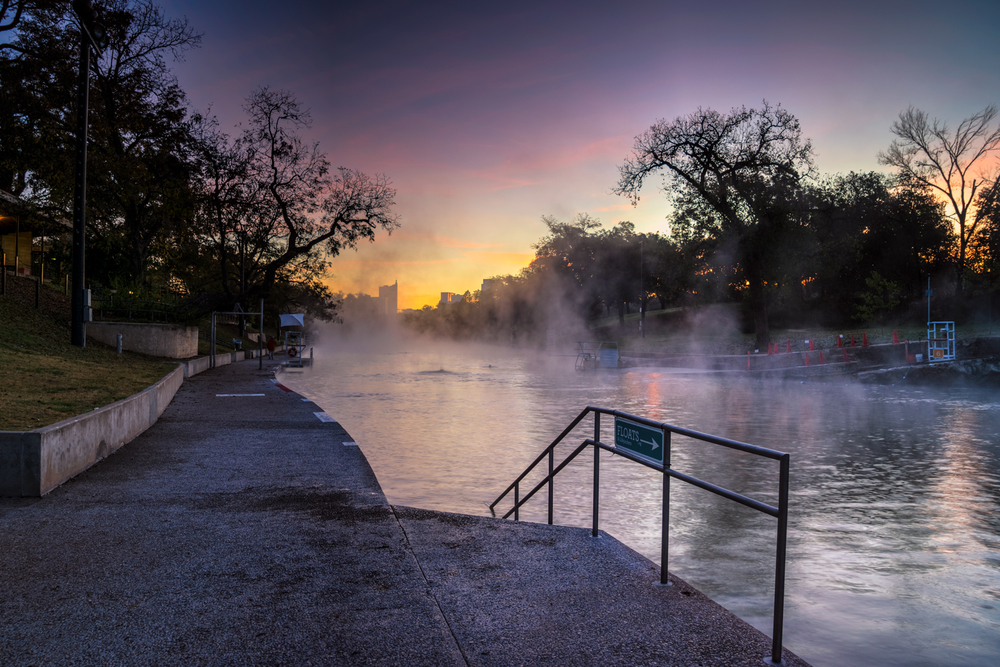 another view of barton springs pool at sunrise with mist rising into the air!