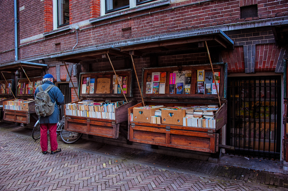 A gentleman browses books at an open-air book market in Amsterdam