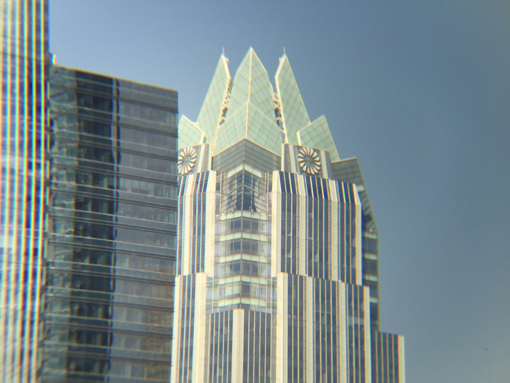 A closeup of the Frost Bank Building in downtown Austin, shot from the same spot as the photo on the left