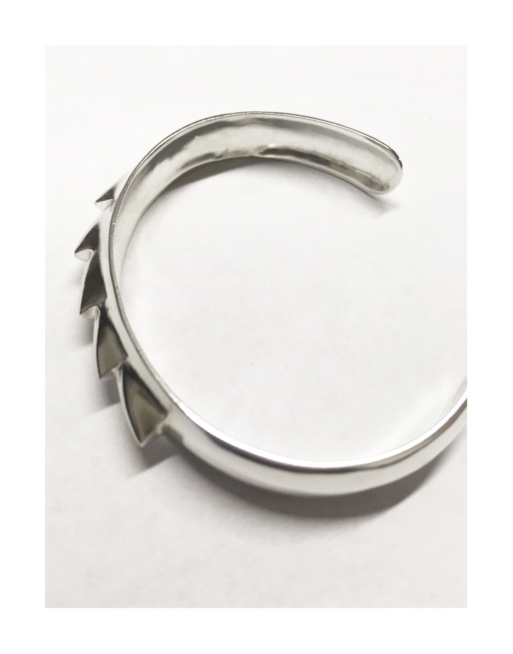 Ness bracelet  Recalling the pointed look of the saw/disc, the bracelet adorns itself with a sharp teeth that smoothly blend out of a central curvature. Ideal for those times when the mere suggestion of aggressiveness is deterrent enough.