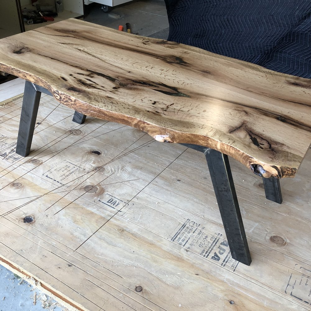 Lively-Edge - Custom Live-Edge coffee table with steel legs. This Oak log was milled by myself 3 years ago. It was a wind-fallen tree destined for the firewood pile in my parents yard. It is very rewarding to see a piece through this life cycle. I hope you can enjoy it as much as I did making it.Only 1 AvailableTop: Solid oak slabLegs: natural steel with wax finish$999 + Tax & Shipping