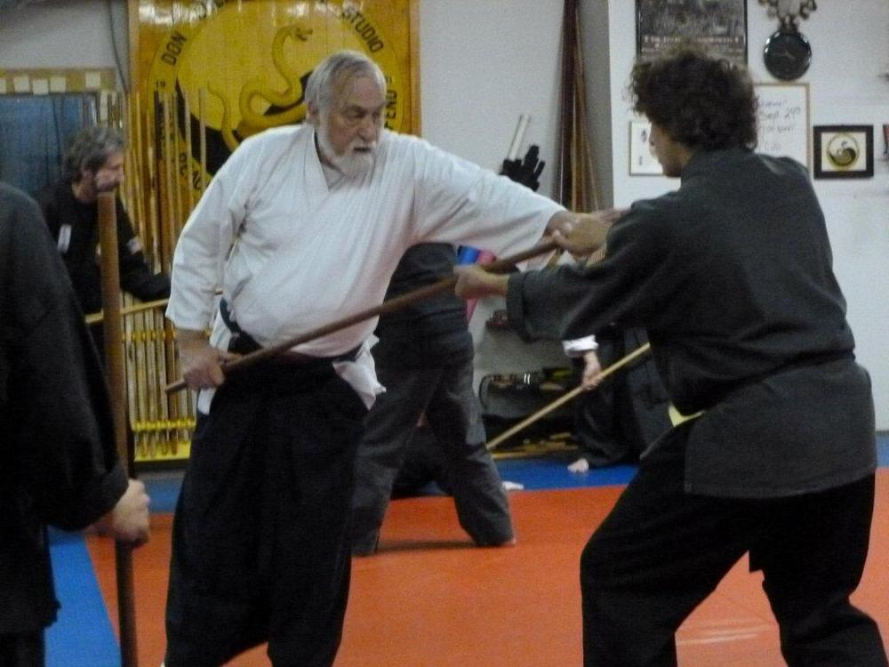 Sensei von Krenner demonstrates kote muwashi with staff to Sensei Don Culp.