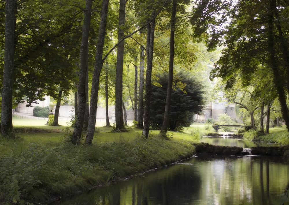 A charming iron bridges spans the small river which runs through the château park