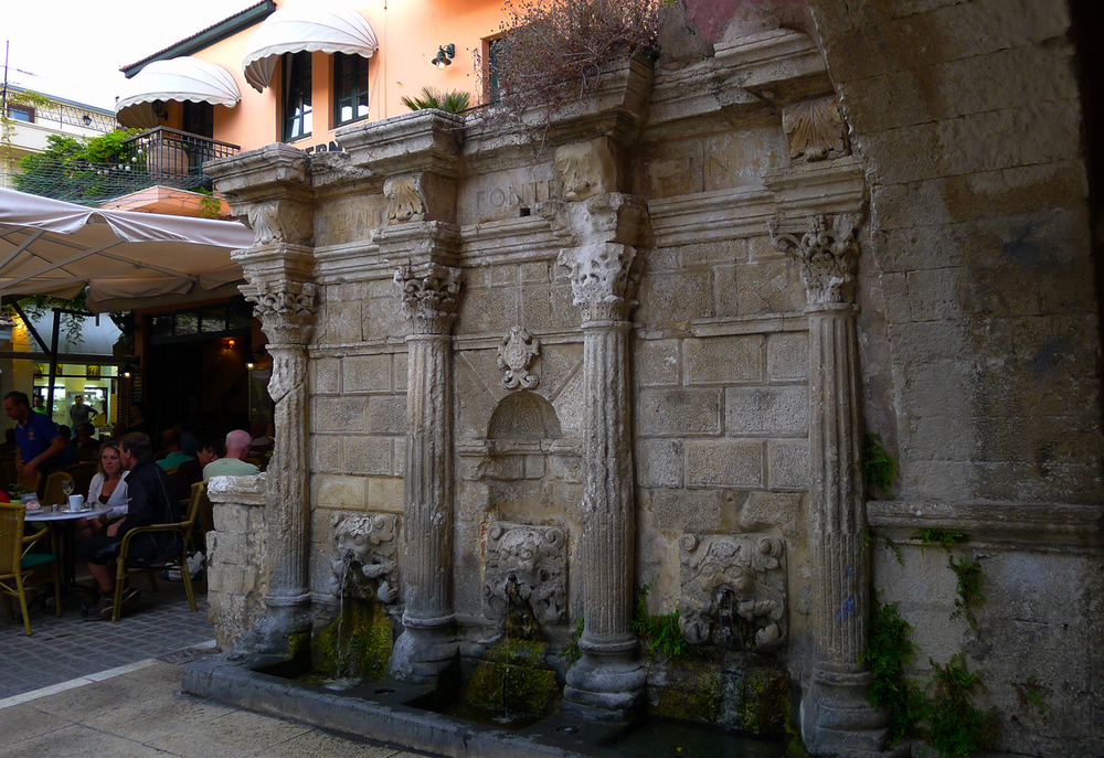 Ancient ruins, fountain and columns next door to a cafe