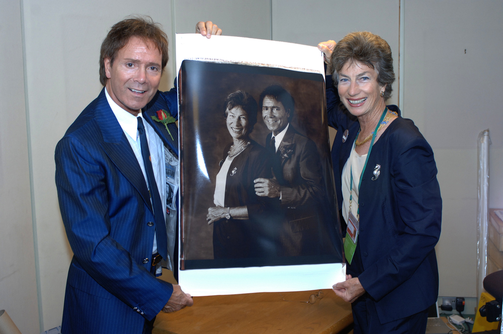 Cliff Richard and Virginia Wade attend the Royal Box at Centre Court and are overwhelmed by the size and detail of the Polaroid.