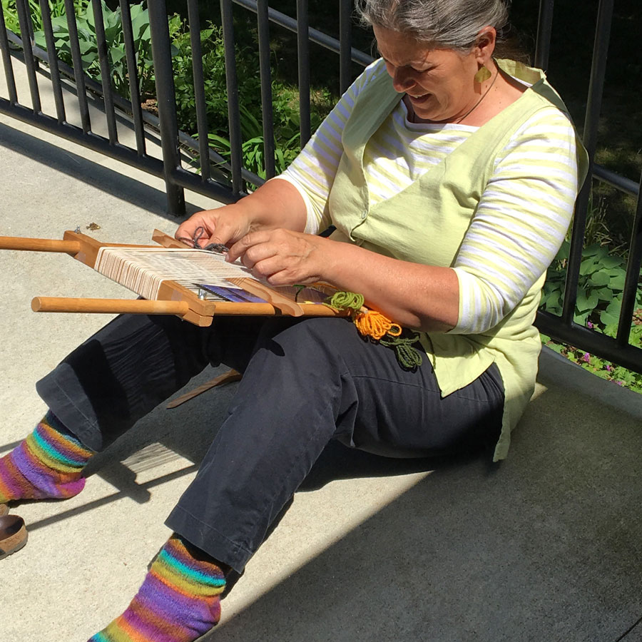 Erin takes the loom into the sunshine in the afternoon. She was an amazing spinner (note socks).