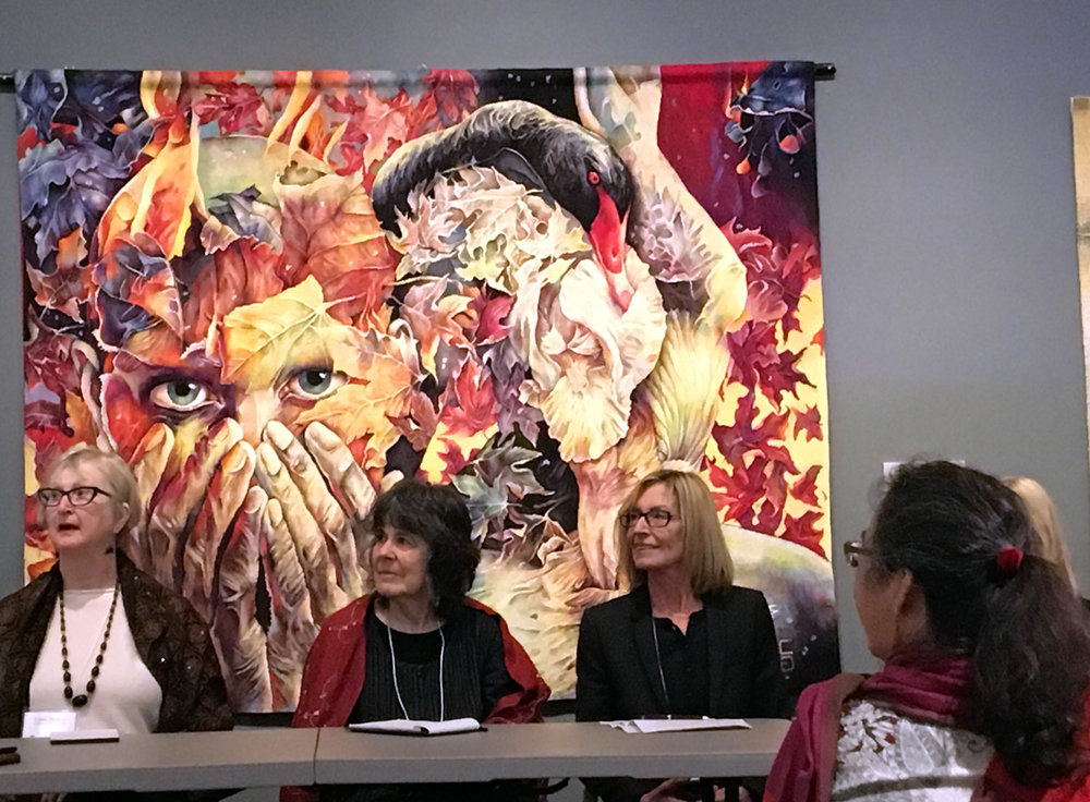 Linda Wallace, Barbara Heller, and Marie-Thumette Brichard participate in an artist panel. Tapestry behind them is Prelude to the Afternoon of a Faun by Gabriela Cristu.