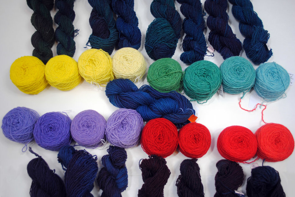 "The original colors are in balls, the ""control"" skein in the center and the resulting dyed yarn next to each original ball color."