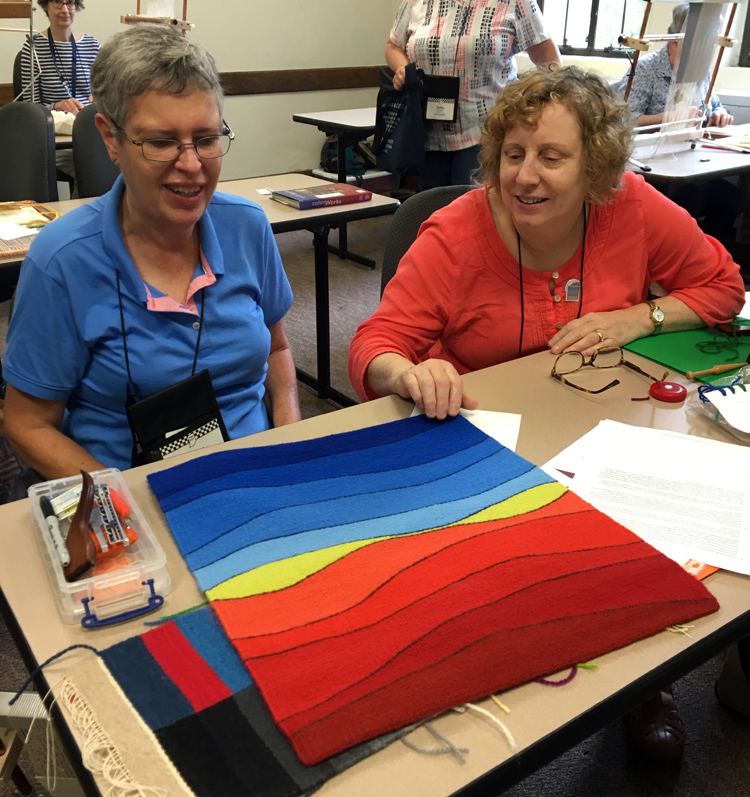 Jenny Chicone (left) talks about a finished tapestry with Nina Kennedy.
