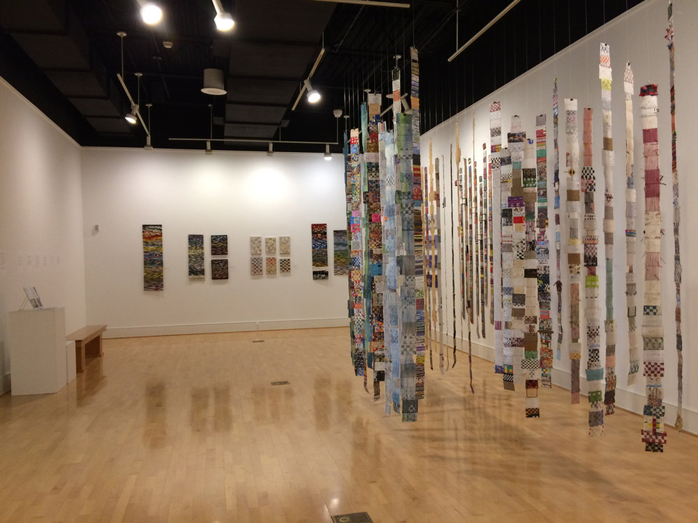 Geri Forkner's work is hanging in the center of the room with diaries by Janet Austin at the back of the room.