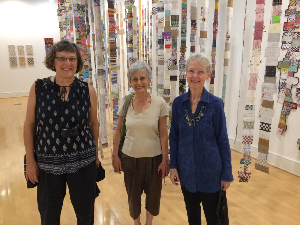 Janet Austin, Geri Forkner, and Tommye Scanlin enjoy the opening of the Time Warp show in front of Geri's work.