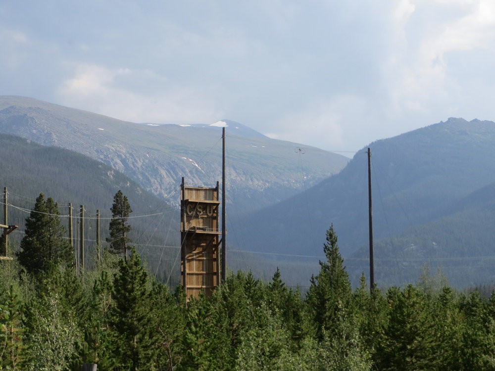 CSU Mountain Campus ropes course with Stormy Peaks behind. I will NOT be jumping from that platform to catch a swinging trapeze (nor will anyone in my group if I have anything to say about it!).