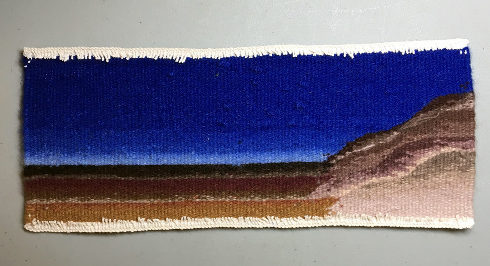 The back of the tapestry with warps stitched on the machine and trimmed off