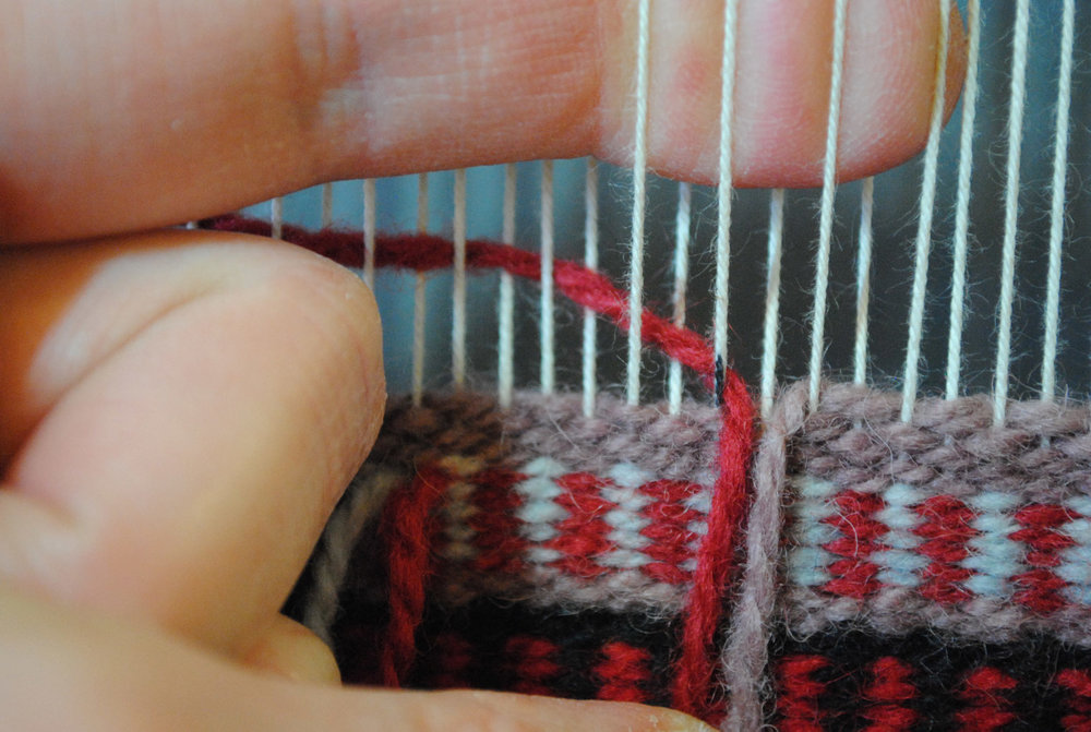 The warp that confuses people is down in this photo--between the red and mauve yarns. My finger is indicating the open shed.