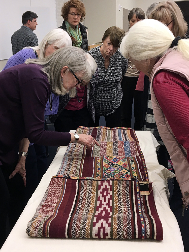 The group looking at a contemporary Peruvian textile with Susan Iverson; from the Avenir Museum's collection