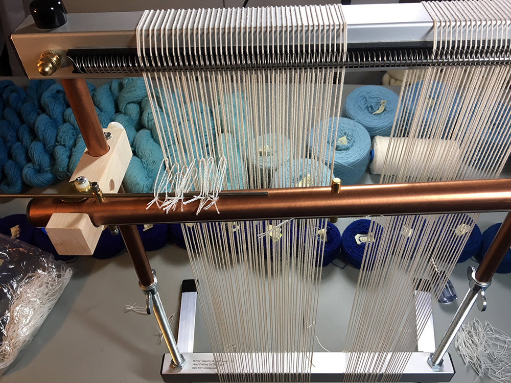 Mirrix loom. Warping coil is at the very top of the image. I am putting heddles on the shedding mechanism in this photo.