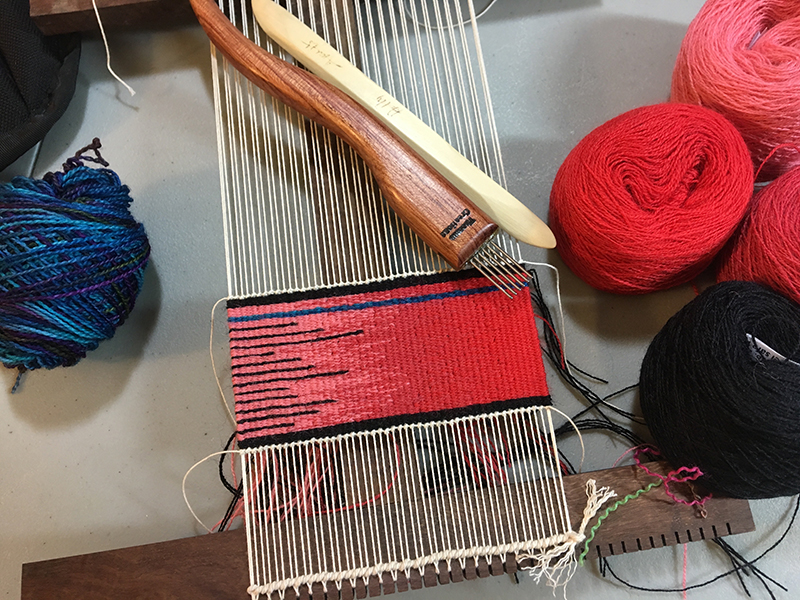 12 epi warp on a 6-dent Hokett loom. Notice the twining at the bottom of the loom.