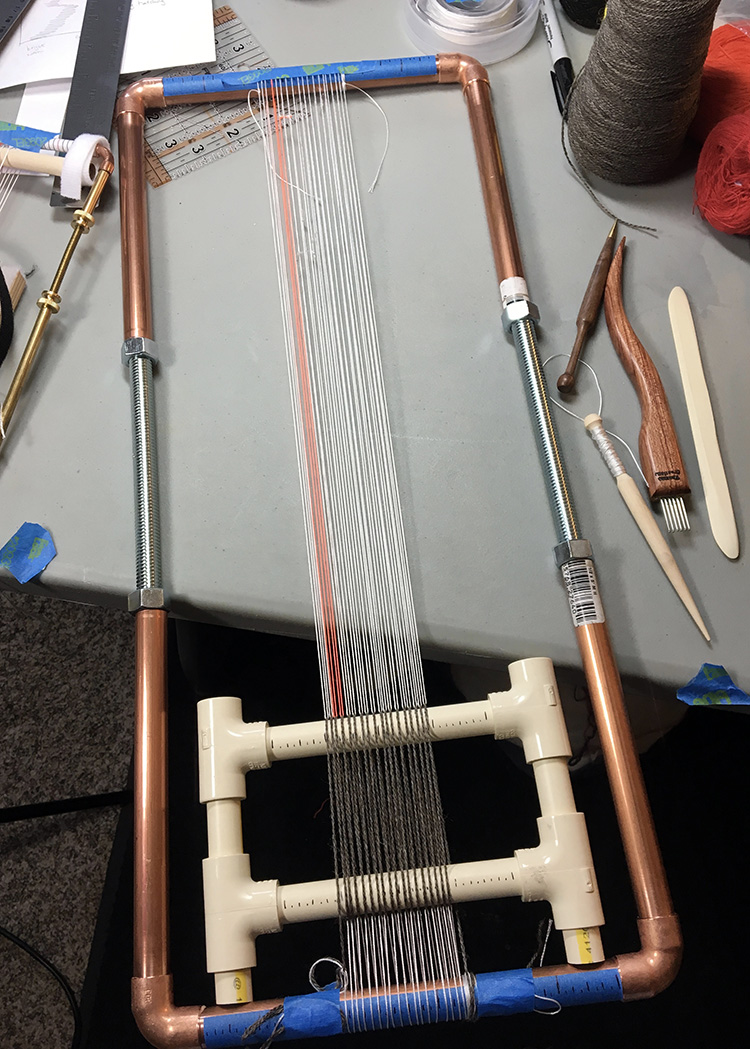 Copper pipe loom warped for four selvedge weaving with PVC jig and brown wool warp.
