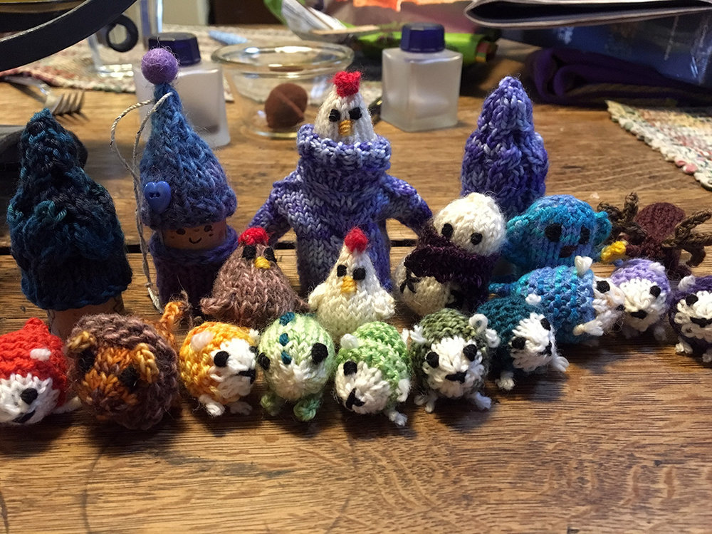 An assortment of creatures including a flock of sheep, a lion, a dinosaur, a monkey, a reindeer, and a chicken pretending the tiny sweater is a holocaust cloak for the castle keep scene from the  Princess Bride.  Crazy chicken!