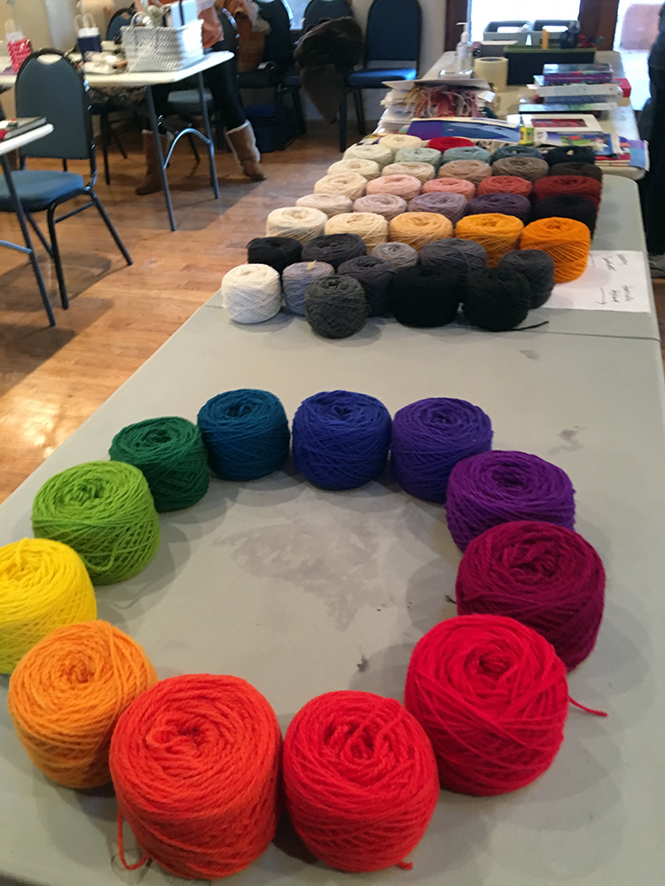 Weaving Southwest yarns lined up behind this color wheel at the recent Taos retreat