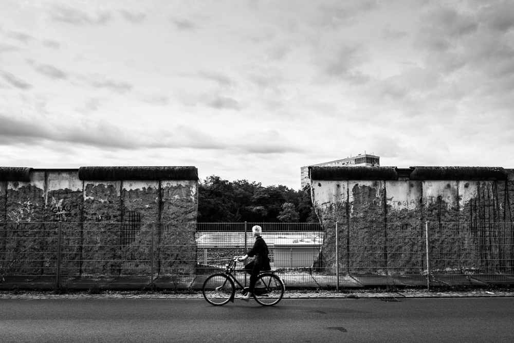 A woman cycles by the Berlin Wall in Germany.