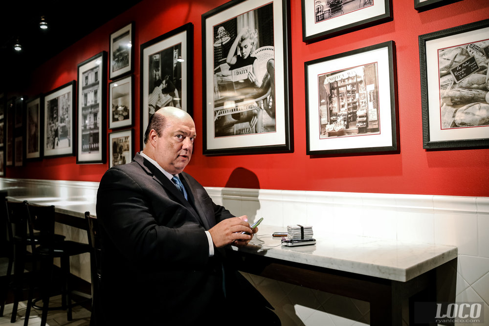 WWE star Paul Heyman caught on his phone, as usual. A Hitchcock-esque shadow looms behind him at the Hard Rock hotel in Las Vegas.