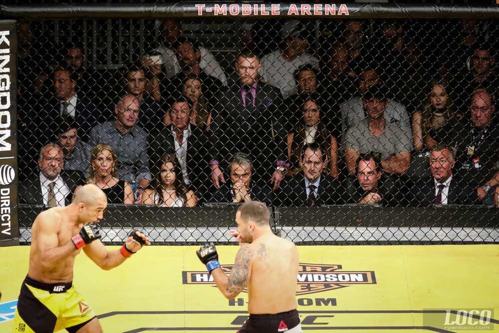 Conor McGregor remains standing and watches intently as Jose Aldo and Frankie Edgar square off at UFC 200.