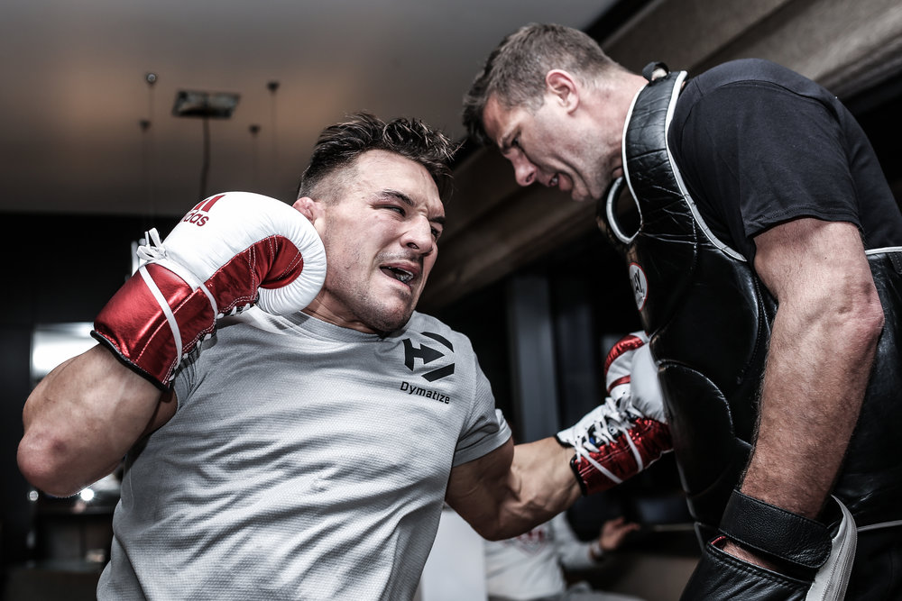 Michael Chandler lands a body shot to coach Henri Hooft in a Vdara hotel room. Often times on UFC fight weeks, rather than search for a gym, a hotel suite will do.