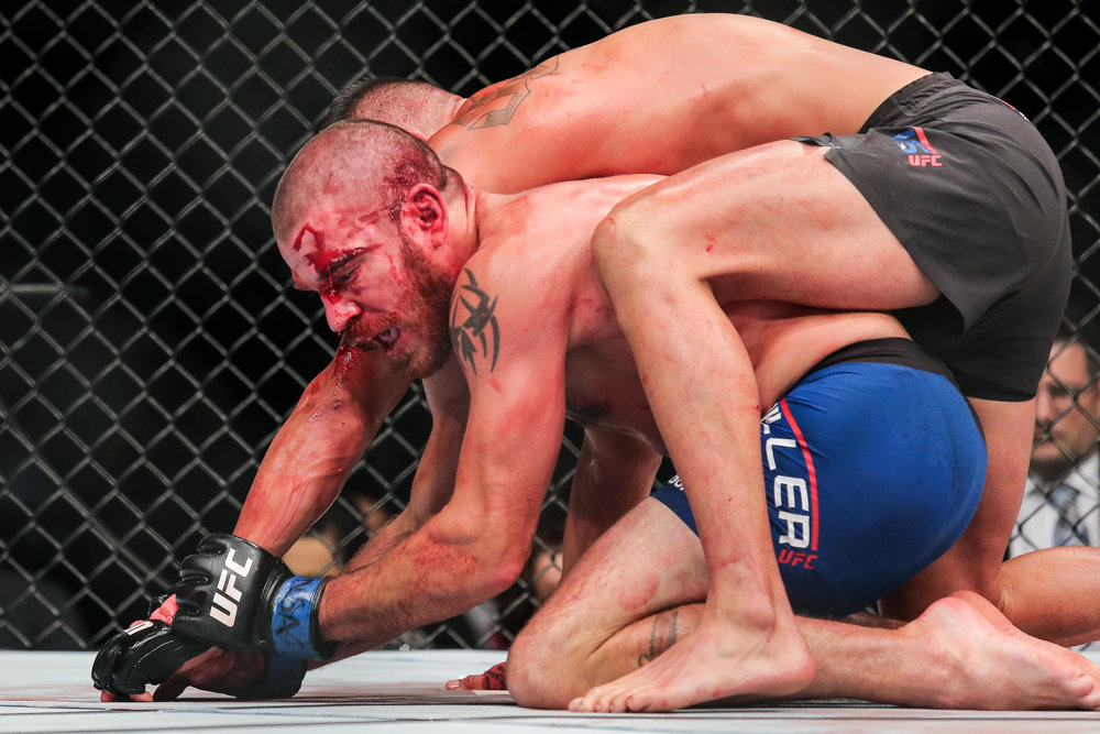 A bloodied Jim Miller dealing with the backpack that is Anthony Pettis at UFC 213.