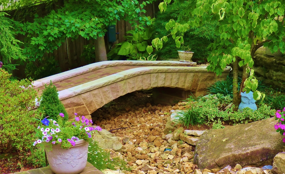 Stone arch bridge with a recessed brick path.     Stone Works by Lee Lindsey St. Louis, MO