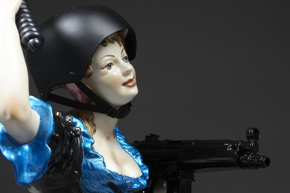 Penny Byrne,  Life if a Riot - Gezi Park , 2013 , Altered vintage ceramic figurine, plastic figurines and leaves, plastic baton, hand grenade and radio, dolls helmet, epoxy resin, enamel paints, metal bolts - H x 760mm W x 420mm D x 410mm
