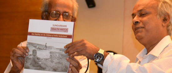 Professors Barun Kanjilal and Rabindranath Bhattacharya present a copy of the Sundarbans Health Watch - Series 1