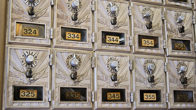 Vintage USPS post office boxes — today boxes open with keys (image is in the public domain)