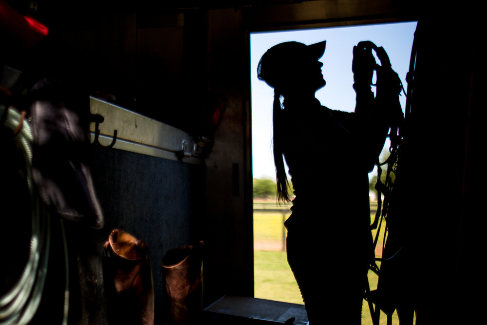 Hudspeth returns a horse bridle to the trailer where she stores all of the tack after a day of exercising the horses.