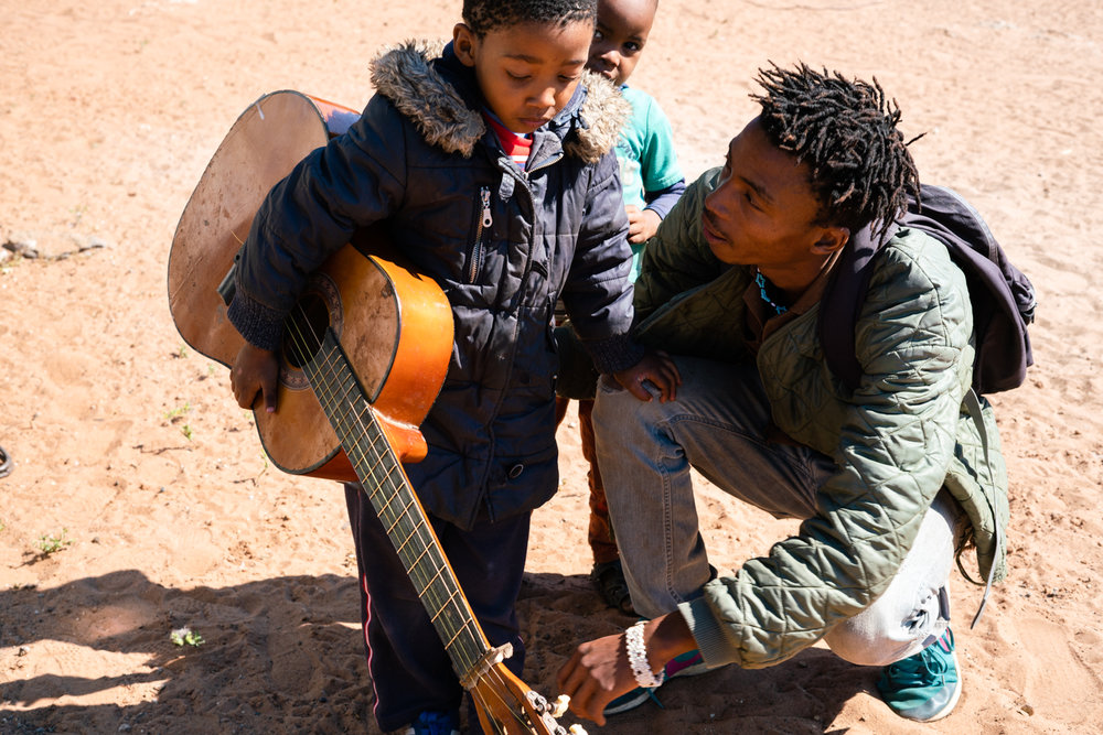 Alphynho talks with his nephew Thabiso while he holds his guitar. Alphynho says he feels like a mentor and role model for his young cousins and other children in the community and they all look up to him.