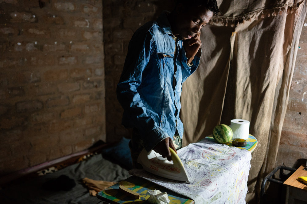 Alphynho irons some hand-painted curtains in his room while on the phone with his girlfriend, who attends tertiary school in Ghanzi, a town about 40 kilometers south of D'kar.