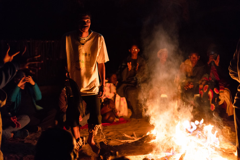 Alphynho performs a traditional dance around the fire for international visitors attending a design summit in D'kar in July 2018.