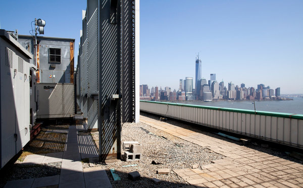 On the rooftop of the Newport Financial Center building in Jersey City.  Six generators that use diesel fuel are in the enclosure.    Credit: Brian Harkin for The New York Times