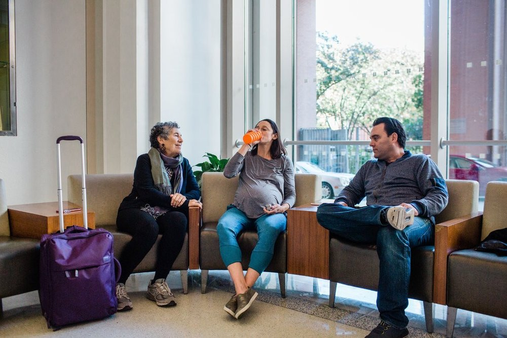From left, Jane Hirschmann, a doula, sits with Lauren Alzamora and her husband, Cartney Curnuck, in the lobby of Mt. Sinai West, which is scheduled to close its birthing center at the end of the year.CreditGabriela Bhaskar for The New York Times