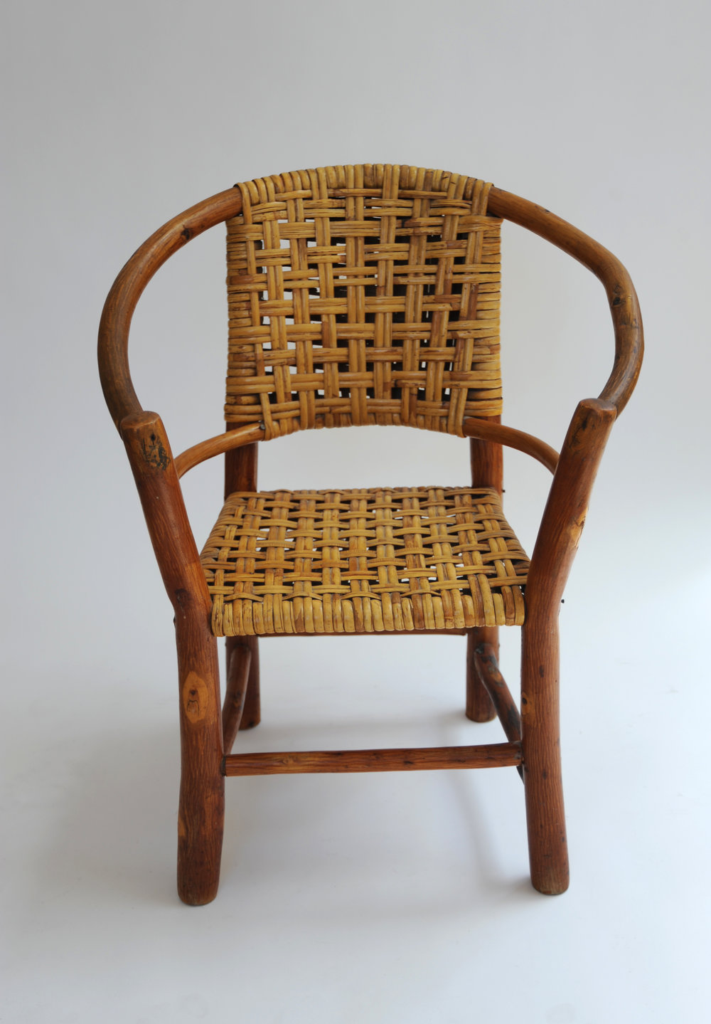 """Adirondack"" Style Child Chair Unknown Designer USA, 1935-1945 Rattan, natural molded ""tree branch"" legs H 24 in, W 19.5 in, D 13 in, SH 12.5 in LIST PRICE: $925 DESIGNER DISCOUNT PRICE: $786.25 LEAD TIME: (Showroom) QUANTITY IN STOCK: 1 ONLINE PLATFORMS: kM Web, Artsy, 1st Dibs"