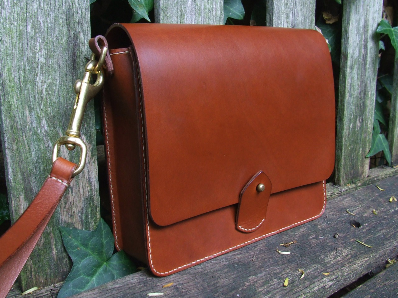 Pochette for Oliver    made out of dark brown vegetable tanned leather   solid brass fittings   hand loop attached to the bag by copper rivet   red suede lining   solid brass zip