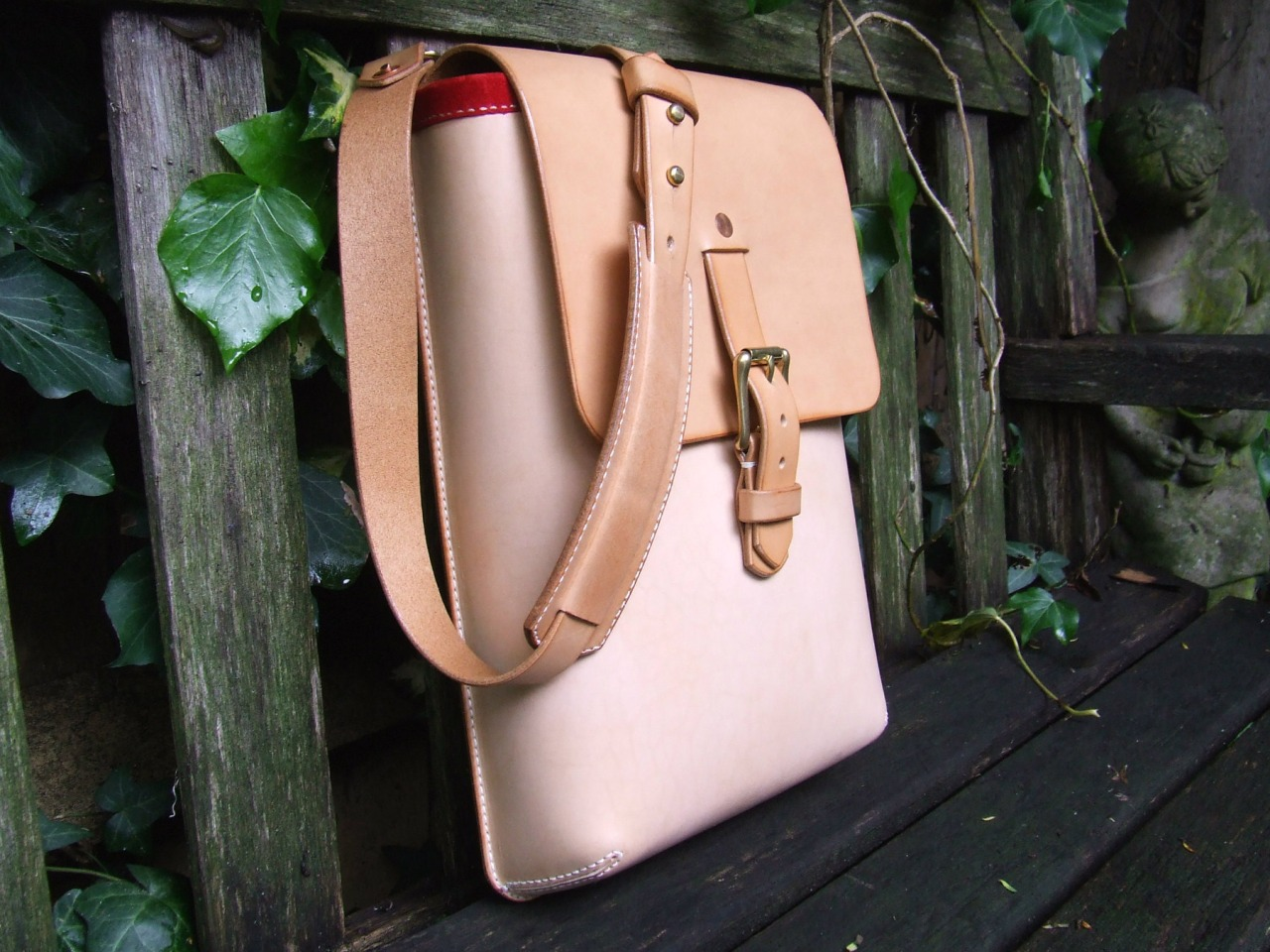 A Messenger Bag: made out of natural vegetable tanned leather copper rivets solid brass fittings red suede lining