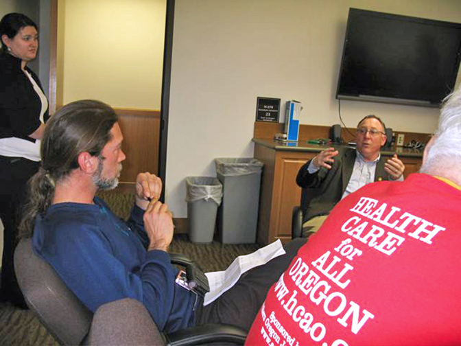 Tony Sanders (blue shirt) listens to Oregon State Representative Peter Buckley.jpg