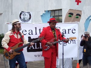 "portland Blues legend Norman Sylvester (right) belts out a tune calling for ""Healing the healthcare blues"" with his bass player Rob Shoemaker during a Feb. 4 Healthcare for All Oregon rally at the Capitol Building in Salem. Photo by Rob Fisher/HealthCare for All-Oregon"