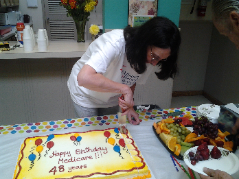 Linda DeLucia, one of the event organizers, cuts the cake.