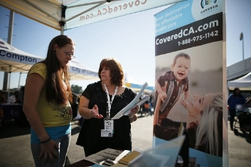 Maria Franco (R) explains health insurance to Violet Lucas-Barajas, 28 years old, at an event to inform people about the Affordable Care Act and donate turkeys to 5,000 needy families, in Los Angeles on Nov. 25, 2013. (REUTERS/Lucy Nicholson)