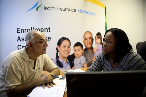 An Obamacare enrollment specialist helps a man sign up for health insurance